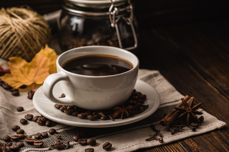 badian: White cup of coffee with various spices, beans and yellow autumn leaves on dark wooden background