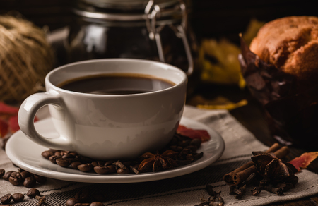 badian: Cup of Coffee with Autumn Leaves, Sweet Muffin, Some Condiment and Equipment Stock Photo