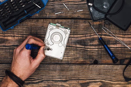 Male Hand with Screwdriver Disassemble Hard Drive