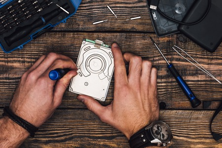 Two Male Hands with Screwdriver Disassemble Hard Drive Stock Photo