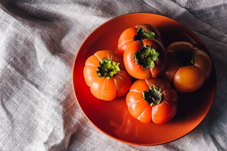 Some Persimmons on Orange Plate. High Angle View