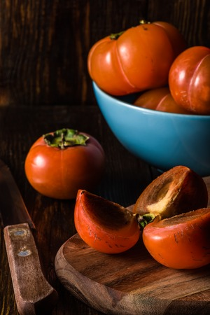Sliced Persimmon for Three with Knife and Some Fruits in Blue Bowl on Background. Vertical.