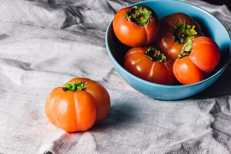 Ripe Persimmons in Blue Bowl Bowl ande One on Table