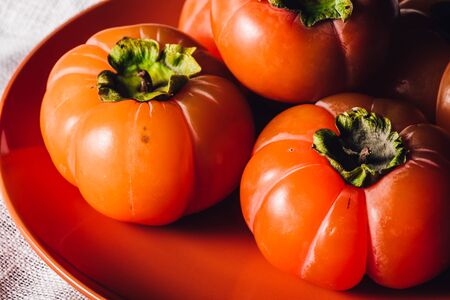 Ripe and Sweet Persimmons on Orange Plate. Close up View Stock Photo