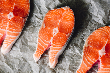Raw Salmon Steaks on Parchment Paper. View frrom Above.