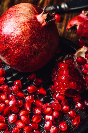 Whole Pomegranate and Opened One wiith Seeds on Metal Plate. Vertical Orientation. Stock Photo