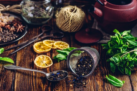 Tea in Strainer and Spoonful of Tea with Fresh Mint, Lemon Slices. Tangle with Two Jars and Teapot on Backdrop.
