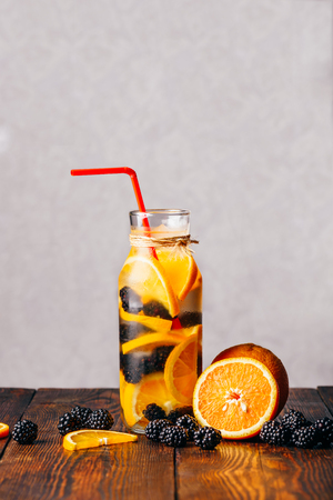 Red Straw in Bottle of Chilled Water Infused with Sliced Raw Orange and Fresh Blackberry. Ingredients on Wooden Table. Imagens