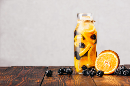 Bottle of Detox Water Infused with Sliced Raw Orange and Fresh Blackberry. Ingredients on Wooden Table. Imagens