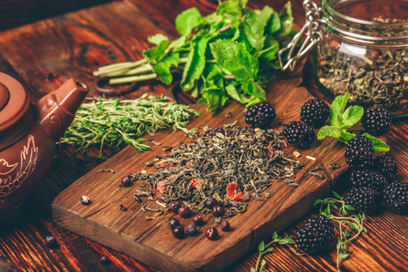 Heap of Dry Green Tea and Fresh Blackberries on Wooden Cutting Board. Bundles of Mint and Thyme Leaves. Clay Kettle.