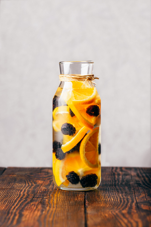 Bottle of Detox Water Infused with Sliced Raw Orange and Fresh Black berry.
