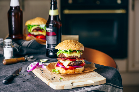Burger with Two Beef Patties, Cheddar Cheese, Bacon, Iceberg Lettuce, Sliced Tomatoes and Red Onion on Cutting Board. Stock fotó