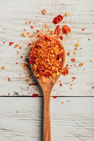 Spoonful of crushed red chili pepper over wooden background