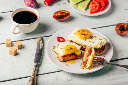 Bruschettas with vegetables and fried egg on white plate, cup of coffee and some fruits over wooden background. Healthy food concept.