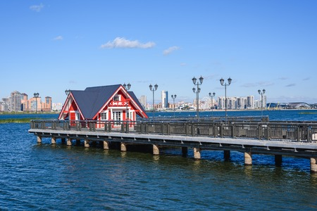 Little red house on pier. High-rises buildings on background.