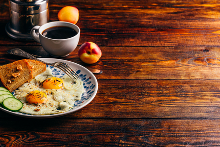 Breakfast toast with fried eggs with vegetables on plate and cup of coffee with fruits over dark wooden