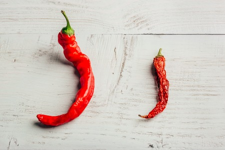 Two red chili peppers, fresh and dry, over wooden Stock Photo