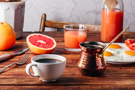 Breakfast with turkish coffee, fried eggs, juice and fruits over wooden table