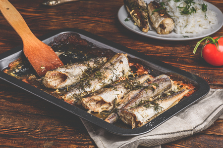 Baked fish carcasses on baking sheet over wooden surface Foto de archivo - 119763974