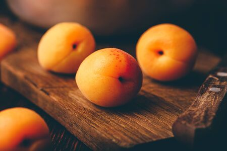 Mellow apricots with knife over old wooden cutting board and metal bowl with fruits