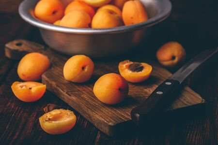 Mellow apricots with knife over old wooden cutting board and metal bowl with fruits Stok Fotoğraf - 132074290