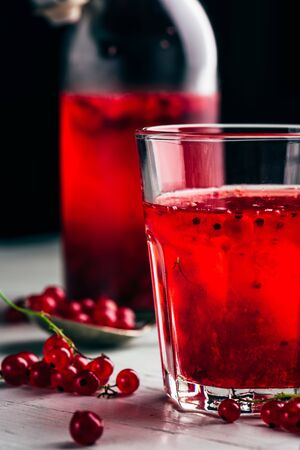 Table glass of infused water with fresh red currant
