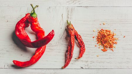 Fresh, dried and crushed red chili pepper over colored wooden background