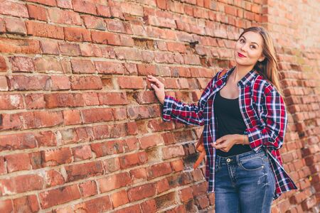 Portrait of young woman in checkered shirt and blue jeans standing against brick wall