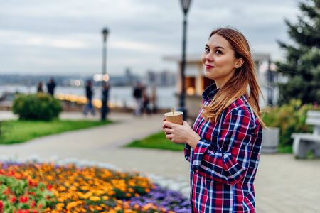 Coffee on the go. Beautiful young woman holding coffee cup and smiling in the park