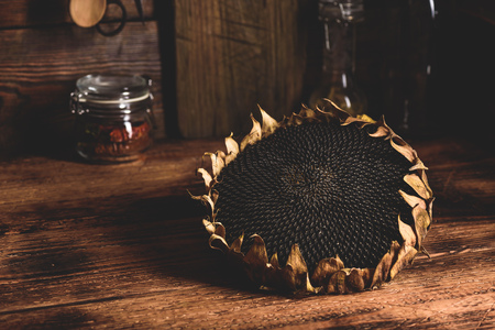 Dried sunflower head on the wooden table Фото со стока