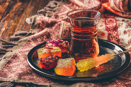 Thé en verre armudu avec délice oriental rahat lokum sur plateau en métal sur surface en bois et nappe