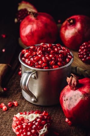 Metallbecher voller Granatapfelkerne. Ganze Früchte und Granatapfelstücke auf dunkler Holzoberfläche. Standard-Bild