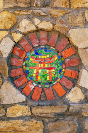 Circular mosaic religious symbol of Shinto on stone wall.
