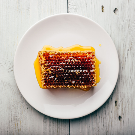 Top view of delicious yummy honeycomb on bright plate over light wooden background