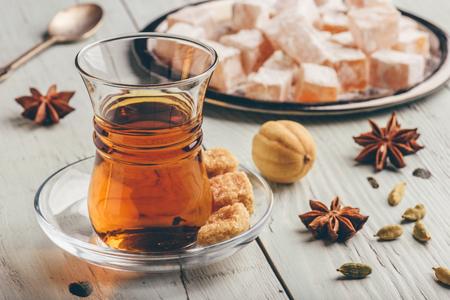 Tee im arabischen Glas mit türkischem Genuss Rahat Lokum und verschiedenen Gewürzen auf Holzoberfläche