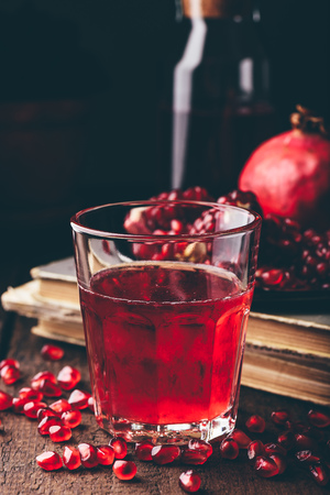 Drinking glass with pomegranate cocktail on wooden table