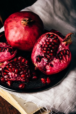 Ripe and juicy pomegranate fruit on metal plate 스톡 콘텐츠