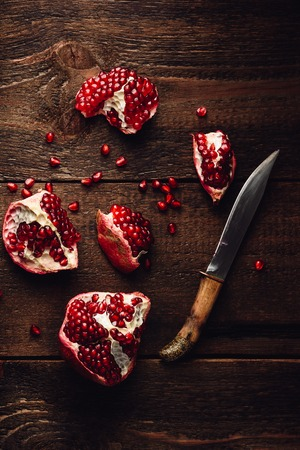 Pomegranate pieces with knife on rustic wooden surface. View from above