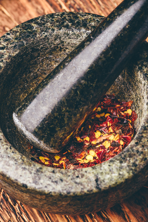 Red chili pepper grinded in mortar. High angle view 免版税图像