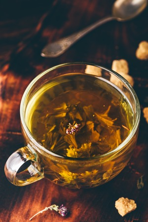 Cup of green tea with brown tea sugar on a wooden background