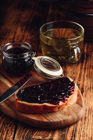 Toast with berry jam on cutting board and cup of green tea