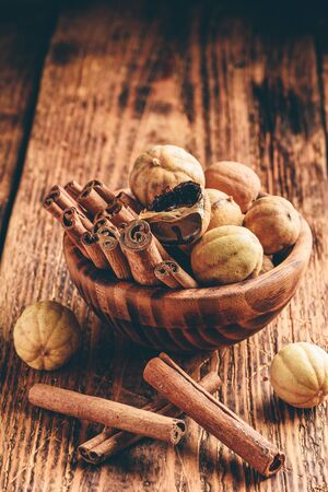 Cinnamon sticks and dried limes in wooden bowl on rustic table