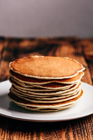 Stack of american pancakes on white plate over wooden table