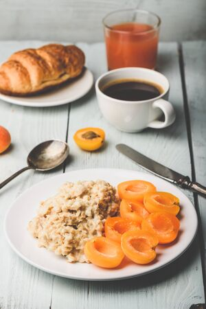 Breakfast set. Porridge with sliced apricot, cup of coffee, glass of grapefruit juice and croissant