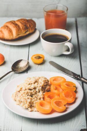 Frühstücksset. Porridge mit geschnittenen Aprikosen, Tasse Kaffee, Glas Grapefruitsaft und Croissant