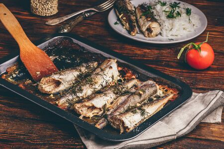 Baked fish carcasses on baking sheet over wooden surface Фото со стока