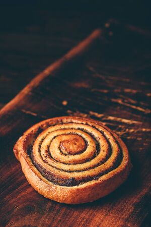 Sweet roll with poppy seeds on rustic wooden surface Imagens