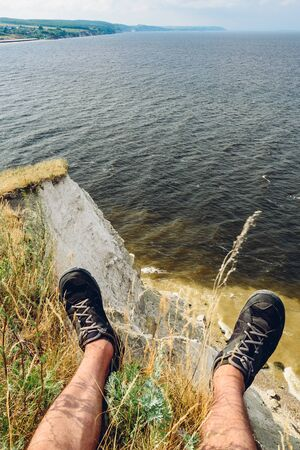 POV point of view of man sitting on the edge of cliff looking down at the river
