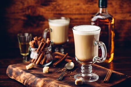 Coffee with Irish whiskey and whipped cream in glass on rustic wooden surface