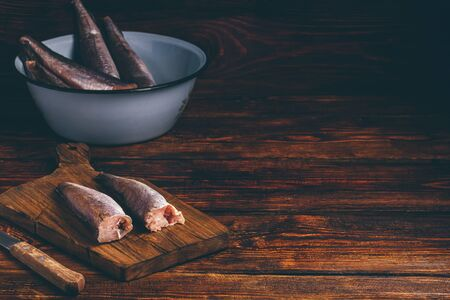 Hake carcasses on cutting board with knife and bowl over wooden surface Imagens